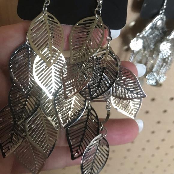 Multiple silver feather design drop earrings.
